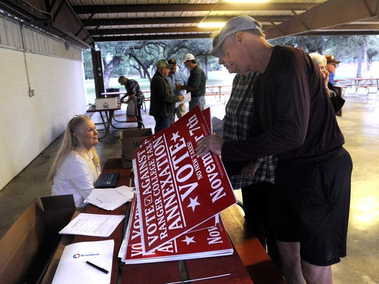 """Sammie Courington picks up a campaign sign for voting against the proposed Ranger College Tax Annexation, during a meeting at Riverside Park in Brownwood Sept. 28, 2017. Courington is retired and lives at Lake Brownwood, he said, """"I don't want my taxes to go up, we live on a fixed income, and this is a forever tax. If it passes, it'll never go away."""""""