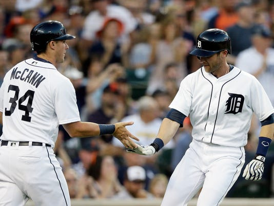 Detroit Tigers' James McCann (34) and Ian Kinsler high-five each other after they scored during the fifth inning of a baseball game against the Cleveland Indians, Friday, June 24, 2016, in Detroit. (AP Photo/Carlos Osorio)