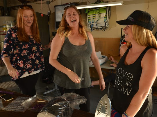 """Donnalee Shewmacke, from left, and her sister Denelle Rutherford wind it up for the day with Christa Morehouse as they and other moms volunteer to make 250 """"#momtribe"""" hats by Sunday."""