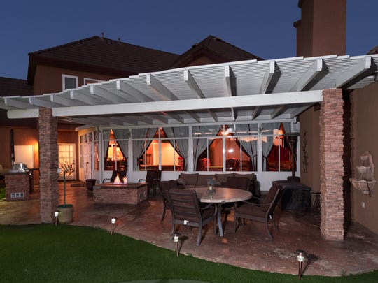 The backyard features a built-in barbecue with tile