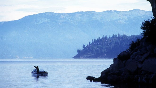 A fisherman casts while fishing at the base of Cave Rock at Lake Tahoe.