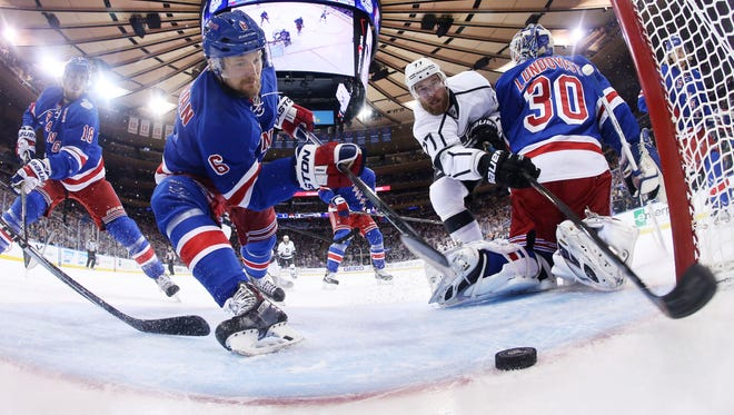 Rangers defenseman Anton Stralman (6) reaches to save the puck from crossing the goal line as Los Angeles Kings center Jeff Carter (77) tries to score from behind goalie Henrik Lundqvist (30) in the first period Wednesday.