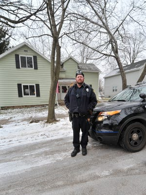 Wausau Police officer Dave Prokop poses Saturday afternoon, Dec. 20, 2014, at his house in Wausau.