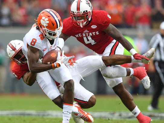 Clemson wide receiver Deon Cain (8) is brought down