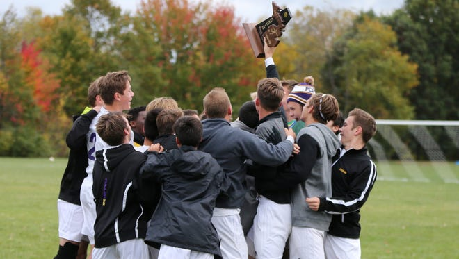 Plymouth Christian Academy's varsity boys soccer team hoists the Division 4 district trophy high in the air after Friday's victory over Lutheran Westland.