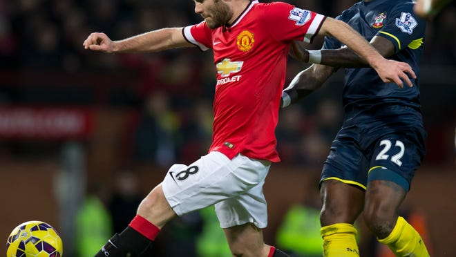 Manchester United's Juan Mata, left, keeps the ball from Southampton's Eljero Elia during the English Premier League soccer match between Manchester United and Southampton at Old Trafford Stadium, Manchester, England, Sunday Jan. 11, 2015. (AP Photo/Jon Super)