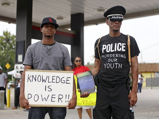 Demonstrators protest the shooting death of 18-year-old Michael Brown in Ferguson, Missouri, August 15, 2014.