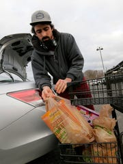 Jack McKee, of Bradley Beach, pushes his grocery cart of groceries packed in recycled plastic bags at Wegmans in Ocean Township earlier this month.