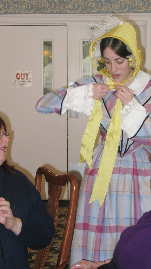 The model describes to an audience member how an accessory was worn back in the 19th century.