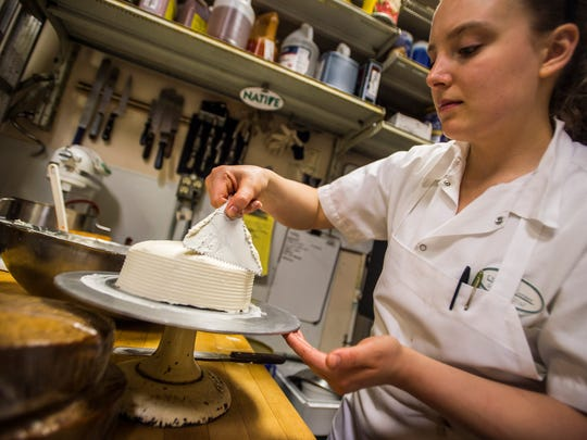 Head of Pastry Rebekkah Deak finishes off icing a cake at the Chef's Corner in Williston on Tuesday, April 18, 2017.