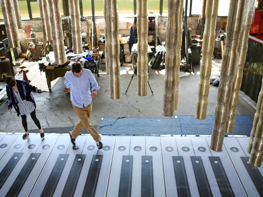 The Enquirer's Arts reporter Carol Motsinger and RetroCincinnati reporter Joel Beall play the foot piano at Verdin Company Wednesday, April 22, 2015. The 19 foot long piano will be installed at Smale Riverfront Park as part of P&G Go VibrantScape.