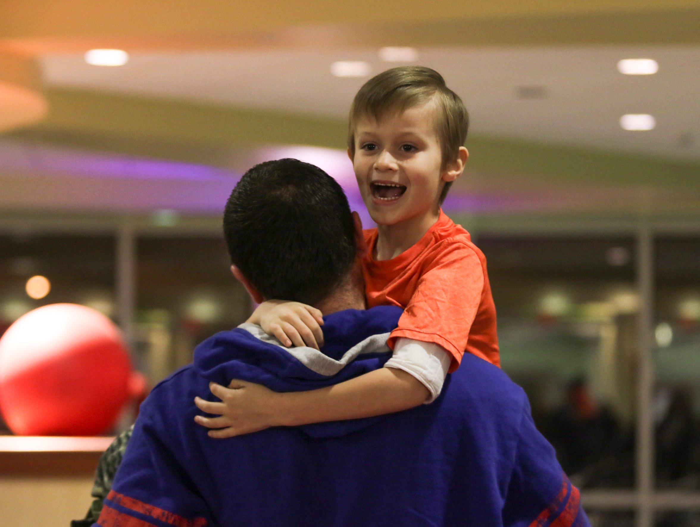Noah Coffman, 6, is carried by his stepdad Adam Albertson