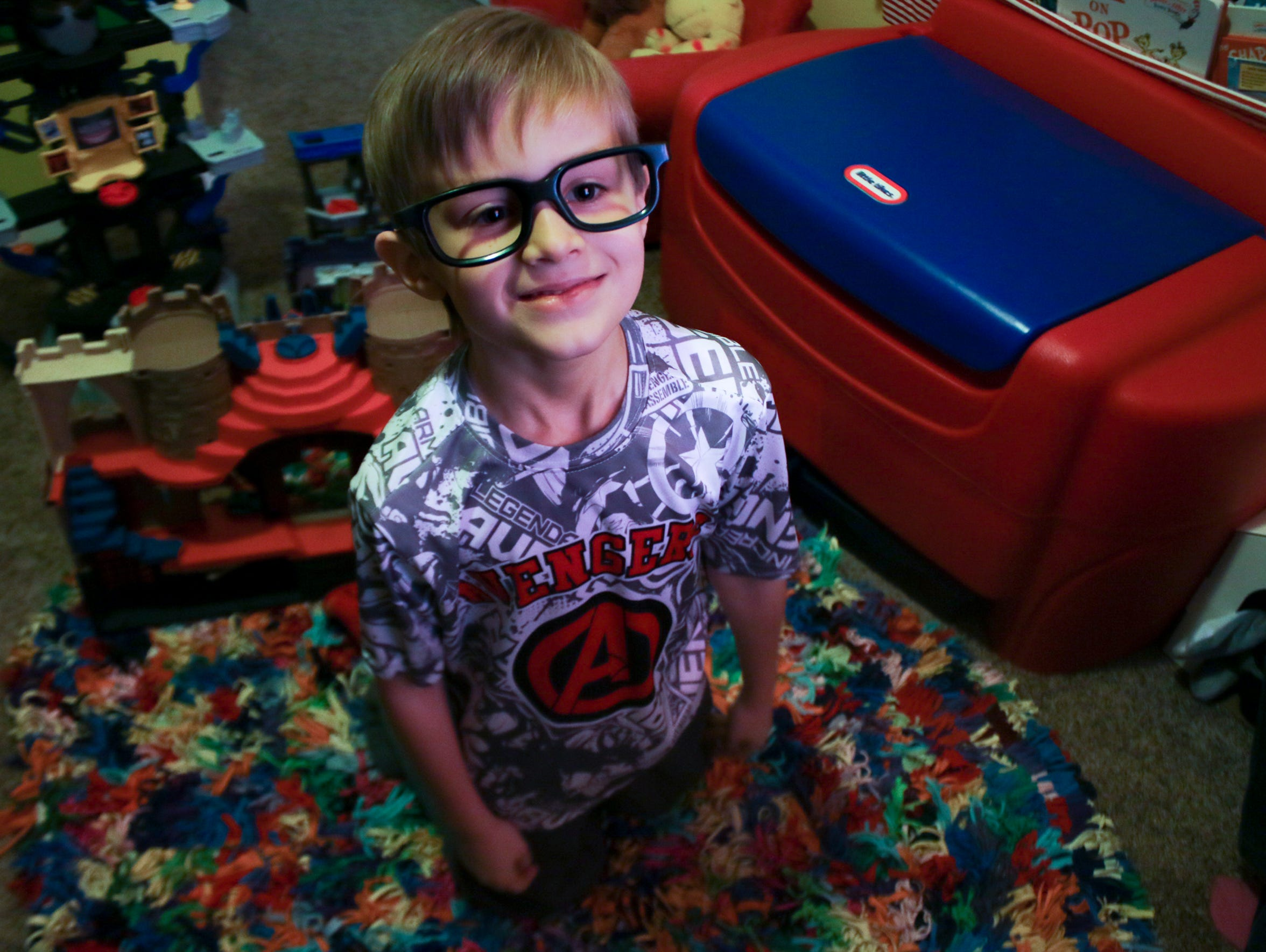 Noah Coffman, 6, poses in his room surrounded by his