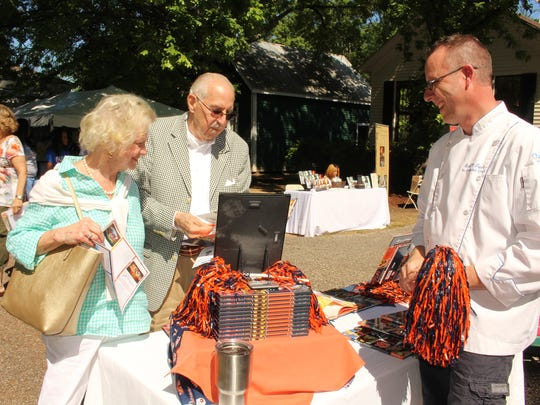 """Sister and Bonner Engelhardt liked what they saw right away and were  among the first to buy """"All in the Kitchen"""" by Chef Emil Topel, right, at the  Alabama Book Festival Saturday morning.  Alvin Benn/Special to the Advertiser."""