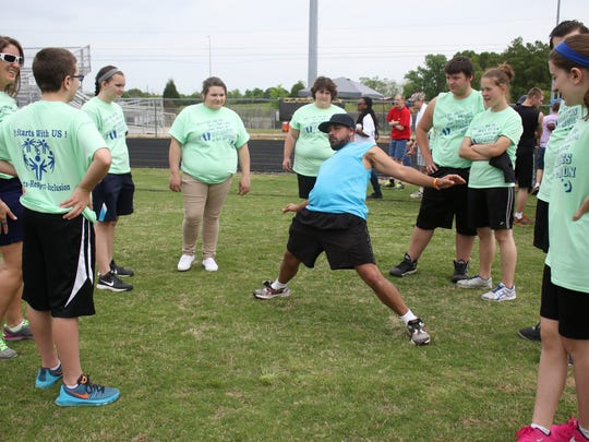 James Porter leads the Stewart County team in stretches during the Special Olympics Spring Games held at Kenwood High School on Friday.