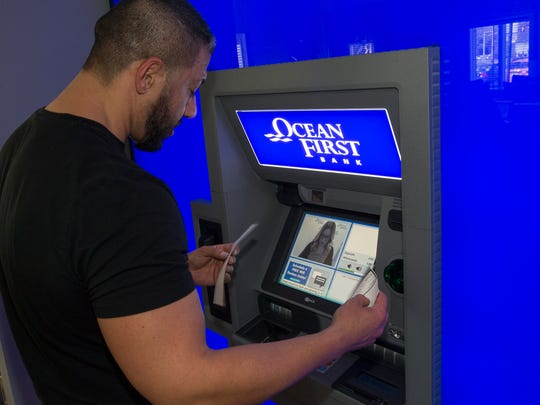 Sevket Yigiter of Jackson makes deposits with teller Patty Nelson using new Personal Teller Machine in the OceanFirst Bank in Jackson. Nelson, who was working in Brick, was able to converse with him as if they were in the same room.