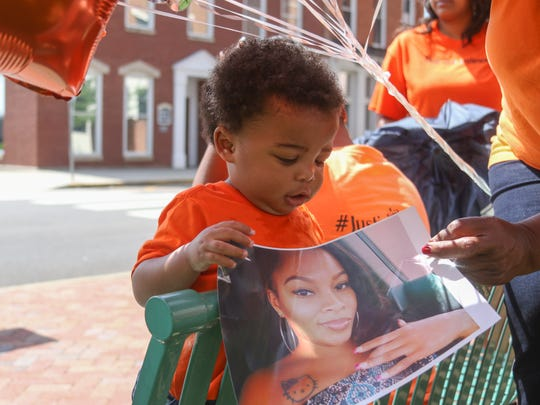 Kyngston Clark, 1, holds a photo of his aunt Princess
