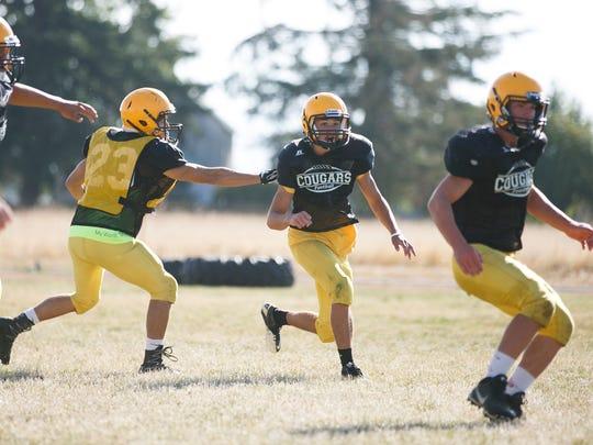 Cascade High School football wide receiver Michael Biddington (center) in a team practice on Monday, Aug. 22, 2016.