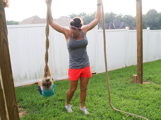 Rachel Hamrick watches as her daughter, Raeah, 3, swings on her Spartan training course at her home.