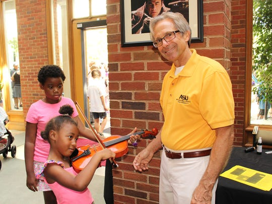Bria Fuller caresses a violin at Saturday's Family Fun Fair and Alabama State University assistant professor of music Michael Zelenak looks on approvingly. Alvin Benn/Special to the Advertiser