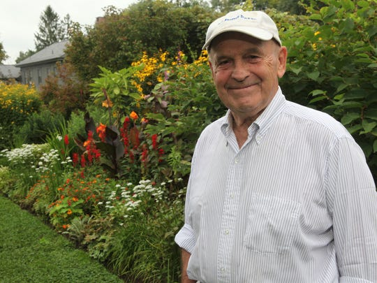 Dick Button poses in the garden at his home in North Salem on Aug. 30, 2013.