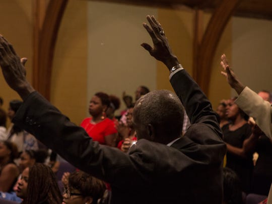 Mike Isom raises his hands during a service in October