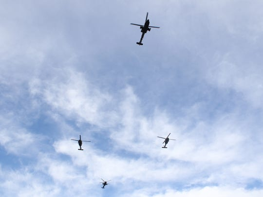 Two Apache helicopters and two Black Hawks fly over