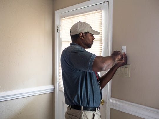 "November 2, 2016 - David Rice, a Comcast technician working with FTS USA, installs a security keypad near the front door of Shakerria Minor-Byers' new home. ""My kids want security cameras too,"" Minor-Byers said. ""We need peace and to feel safe."""