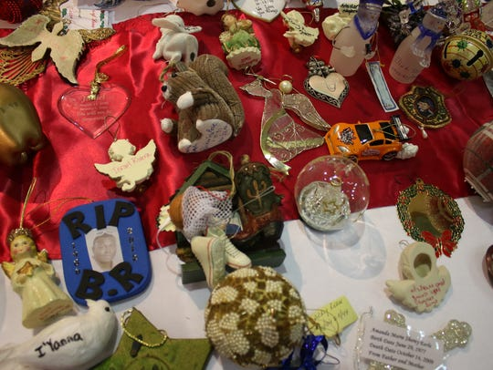 Ornaments in memory of homicide victims sit on a table