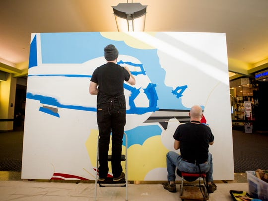 "Jack and Kevin T. Kelly paint the second ""Love Is In the Air"" murals in Concourse B of Cincinnati/Northern Kentucky International Airport Tuesday, December 20, 2016. The local artists and father and son duo worked with BLDG on the Kroger mural on Madison Avenue in Covington."