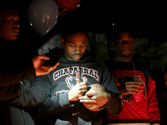 Seite Wyehe, 19, signs a football at a vigil in honor of Richard Nelson on Sunday, Jan. 15, 2017, at Chaparral High School in Las Vegas. Nelson was shot and killed Saturday night in front of his home.