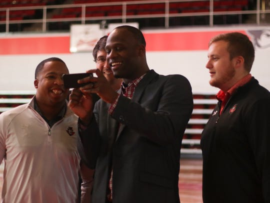 Austin Peay football staff watches a video on a phone