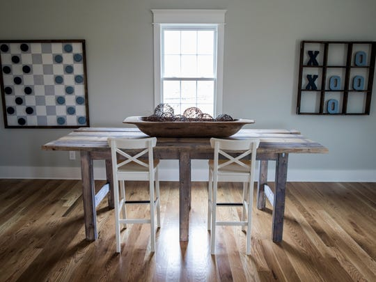 The upstairs game room at the The House For Hope in Franklin features a reclaimed pine table and life-sized checkers and Tic-Tac-Toe boards.