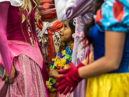 Gabriella Kolisnyk, 5, has her photo taken with Ravenwood High School students dressed as Disney characters.  Ravenwood students raised money all year to give Gabriella a trip to Disney World through Make-A-Wish Middle Tennessee.