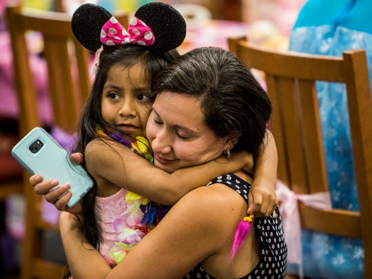 Gabriella Kolisnyk, 5, hugs her mother Norma during a surprise party at Ravenwood High School. Students raised money all year to give Gabriella and her family a surprise trip to Disney World through Make-a-Wish Middle Tennessee.