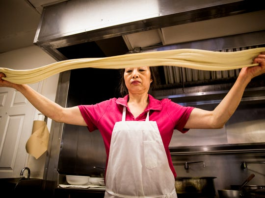 Chef Jin stretches dough to make noodles at Fortune Noodle House in Clifton Friday, April 28, 2017. The hand-pulled noodles are stretched and folded into strands.