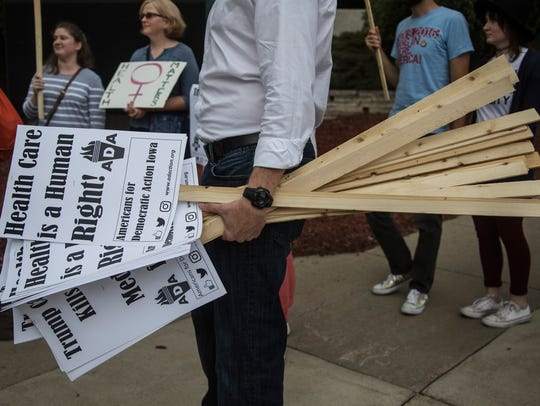 A man holds protest signs outside of the US Cellular