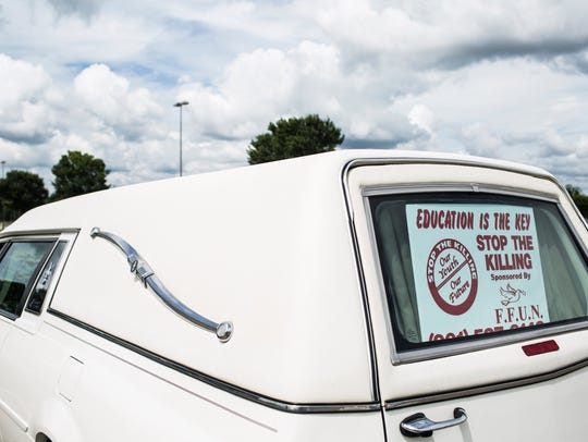 A hearse with a Stop the Killing sign was present at