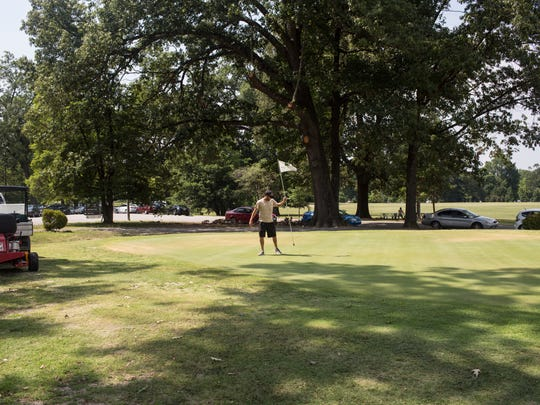 July 25, 2017 - Patrick Canale, facilities manager, pulls the pin from a green before using a rolling machine on the green at the Overton Park Golf Course. Conditions were so bad in 2014 that the golf house staff routinely warned golfers of the situation and offered them a refund if they found the greens too deplorable.