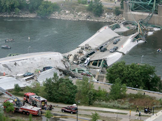 This view shows the Interstate 35W freeway bridge over the Mississippi River after it collapsed Aug. 1, 2007, in Minneapolis, as emergency crews gather. The bridge collapsed during evening rush hour, sending vehicles, tons of concrete and twisted metal crashing into the water.