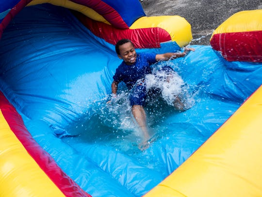 Aarontin Davis, 12, splashes into the water while playing in a large inflatable play place during the National Night Out 2017 event Aug. 1, 2017, at Union Grove Baptist Church.