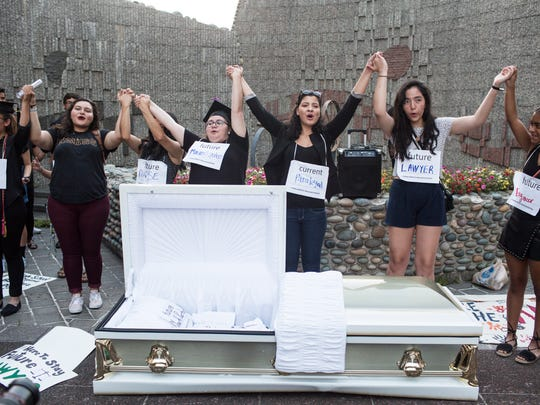 September 04, 2017 - Consideration of Deferred Action for Childhood Arrivals recipients and supporters raise their hands together during a gathering outside of the Clifford Davis Federal Building in downtown Memphis to support the continuation of DACA. DACA gives young immigrants work permits allowing them to avoid deportation. The casket was used to symbolize the dreams that will be buried if DACA is killed.