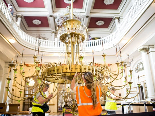 Tiara Waples, of Cleves, removes strands of crystals from the main chandelier in the lobby of Music Hall as the $135 million renovation project began in May 2016. The chandelier and two others, a gift from the late arts patron Patricia Corbett, will be rehung in the renovated Corbett Tower.