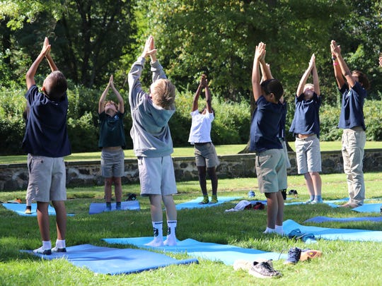 Princeton Academy of the Sacred Heart third graders stretch in yoga pose during the school's recent Wellness Week which is part of a new Mindfulness Program that the Lower School has announced.