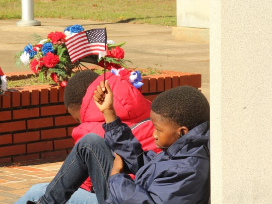Roshad Thomas, 10, holds his small American Flag high as a sign of respect during Saturday's Veterans Day program at Selma's Memorial Stadium. Alvin Benn/Special to the Advertiser