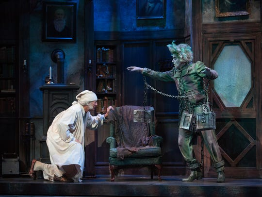 Rodney Clark, left, performs as Ebenezer Scrooge haunted