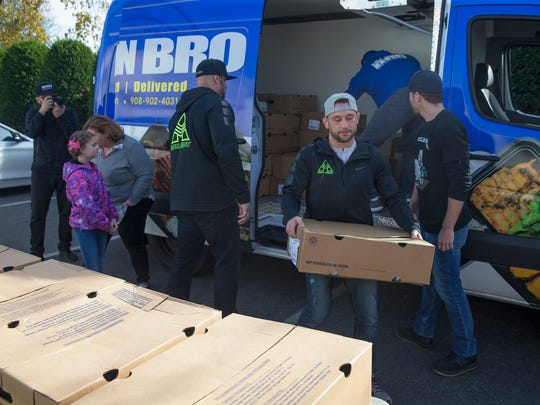Toms River UFC fighter Frankie Edgar and representatives of Eat Clean Bro and The Iron Army unpack a truck full of Thanksgiving turkeys on Tuesday in Red Bank.