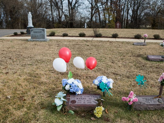 Flowers and balloons adorn the grave of Lorenzen Wright