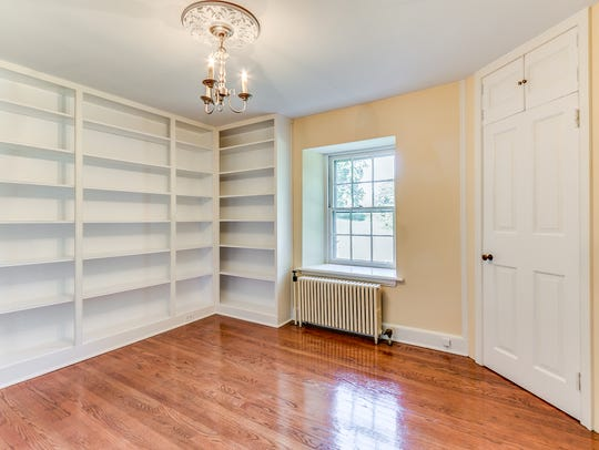 An office features built-in bookcases.