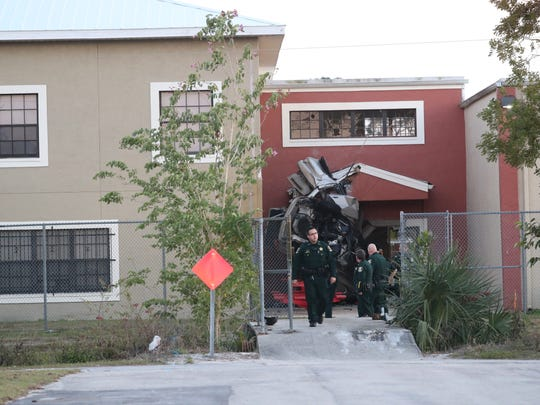 Lee County Sheriff's Deputies examine the scene where a car crashed into Evangelical Christian School at a high rate of speed on Wednesday, January 17, 2018, in Fort Myers. The driver of the car died in the crash.